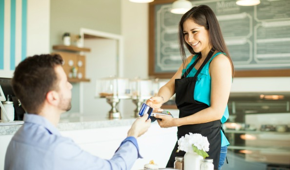 Cute young waitress taking a credit card from a customer while holding a bank terminal